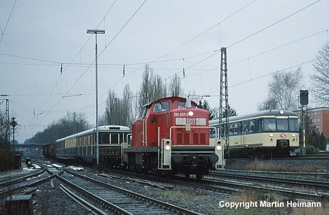 Am 6. Februar 2001 brachte 291 037 den Museumszug von Neumünster nach Hamburg zurück. Um 10.44 Uhr trafen beide im Güterbahnhof Barmbek direkt am Haltepunkt Alte Wöhr ein, den gerade 470 116 in Fahrtrichtung Hauptbahnhof passierte.