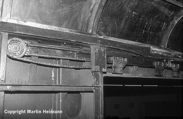 """Der in den Wagen eingebaute und über einen Druckluftzylinder (nicht im Bild zu sehen) betätigte Kettenantrieb der Türen in Stellung """"Tür zu""""."""