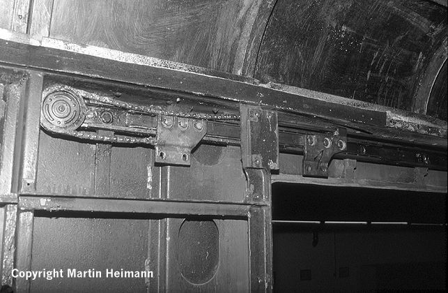 """Der Kettenantrieb in Stellung """"Tür offen"""". Gut zu sehen sind die auf kugelgelagerten Schienen montierten Halterungen, an denen später die Türblätter verschraubt werden."""
