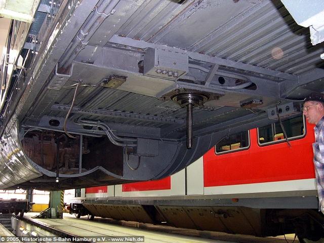 Der Unterboden vom ET171 082a wurde soeben von alten Farbresten befreit und mit neuer Farbe versehen. Dahinter ist in einer Bodenwanne eine der großen Umformermaschinen zu sehen. In Bildmitte der Drehzapfen. Am oberen Bildrand ist die Motorrevisionsklappe zu sehen, durch die ggf. nötige, kleinere Arbeiten am Antriebsmotor ermöglicht werden.