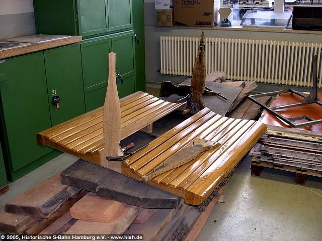 Die Holzbänke des ET171 082b werden einzeln neu gefertigt. Als Maß dienen dabei Originalteile. Hier wird gerade für die Rückenlehnen der Aufbaurahmen eingepaßt. Während hinten ein altes Originalstück eingepaßt ist - ein weiteres Originalstück auf der Bank liegt, ist ein Neubaustück bereits eingepaßt und mit Schraubzwingen probeweise verschraubt.