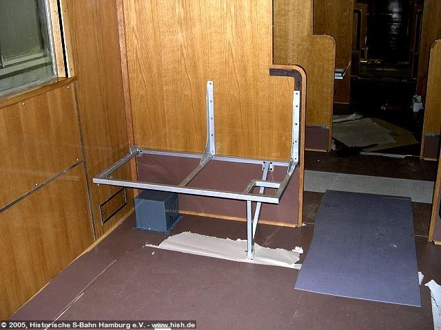 Die ersten Sitzgestelle werden eingebaut. Der Fuß muß mit Blechboden verschraubt werden, um ausreichend Halt zu bekommen. Der Außenrahmen wird ebenfalls mit Gewindeschrauben fixiert. Weitere Fixpunkte werden in das Holz eingebracht. Seitlich bekommt das Gestell Halt durch im Wagenkasten befestigte Bleche zur Montage. Unter dem Sitz der Heizluftkasten und der Schutzbelag des Trennwandrahmens.