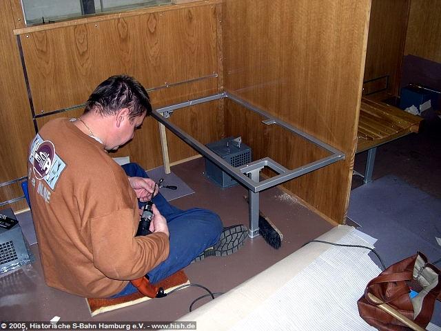Um die Sitzgestelle einbauen zu können, ist eine gute Arbeitsvorbereitung unerläßlich. Hier ist deutlich zu sehen, wie das Gestell abgestützt auf Montage wartet. Als nächster Arbeitsschritt wird die seitliche Fixierung gebohrt, ein Gewinde geschnitten und dann verschraubt. Hinter der Trennwand ist bereits eine Holzbank probeweise aufgelegt.